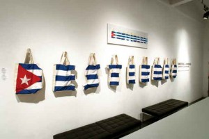 "Destierro, 2011, Cuban flag as canvas shopping bags shaped into letters of D. E. S. T. I. E. R. R. O., 19 ½"" x 100"" x 5 ½"", Ed. 5, and a painting of the installation."