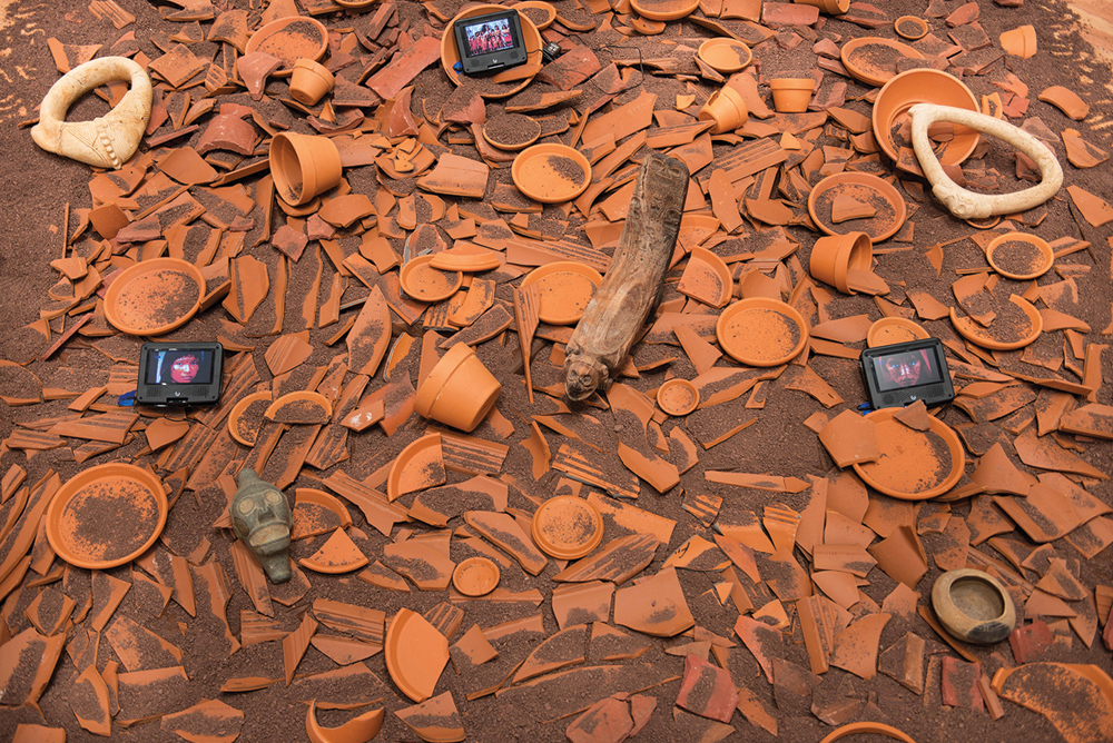 Humberto Castro, Deconstruccion/Reconstruccion, 2013, installation with red clay, terracota shards, video monitors and Taino artifacts, variable dimensions. Courtesy of the Artist, Alfredo Carrada Collection and ArtSpace Virginia Miller Galleries.